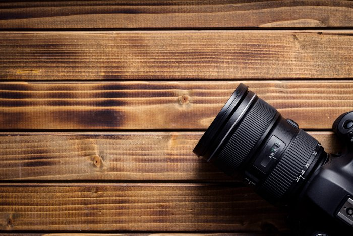 Professional camera with lens on wooden table.