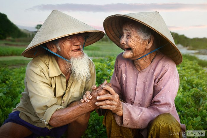 An elderly Asian couple laughing at each other