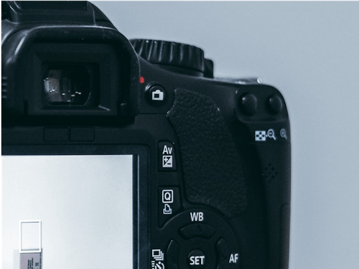 """An image detail of the back of a DSLR camera showing """"AV"""" for Aperture Priority"""