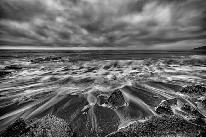 a black and white long exposure image of a seascape