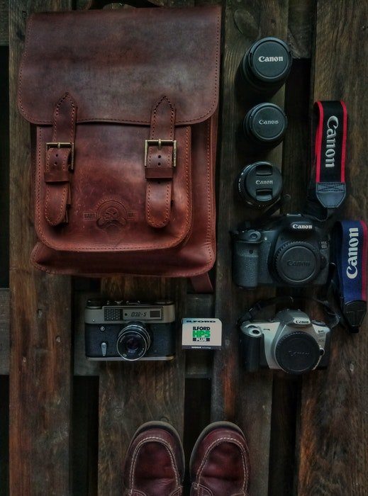 an overhead shot of a leather camera bag and equipment spread across a wooden surface