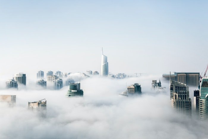 a photograph of city skyscrapers peaking through the clouds