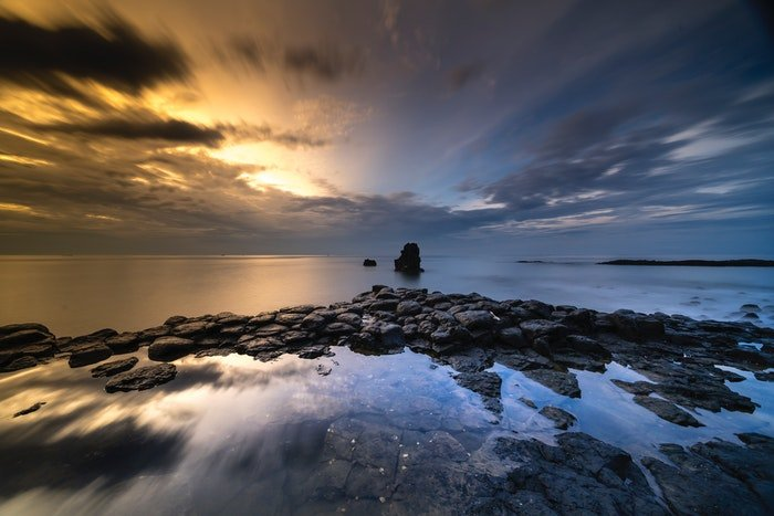 a long exposure photograph of clouds above water and rocks