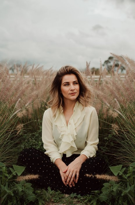 a cloudy day portrait photograph of a woman sitting in a wheat field