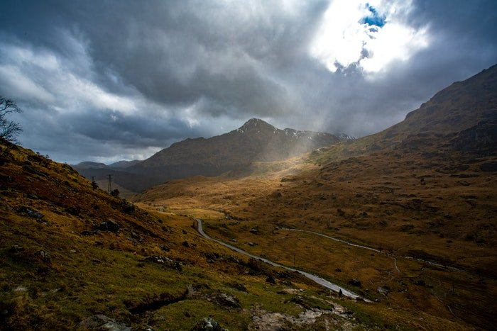 cloudy day photograph of a ray of light cutting through clouds onto a valley