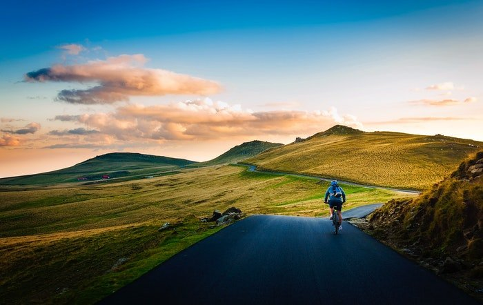 A cyclist on a road in a beautiful countryside area