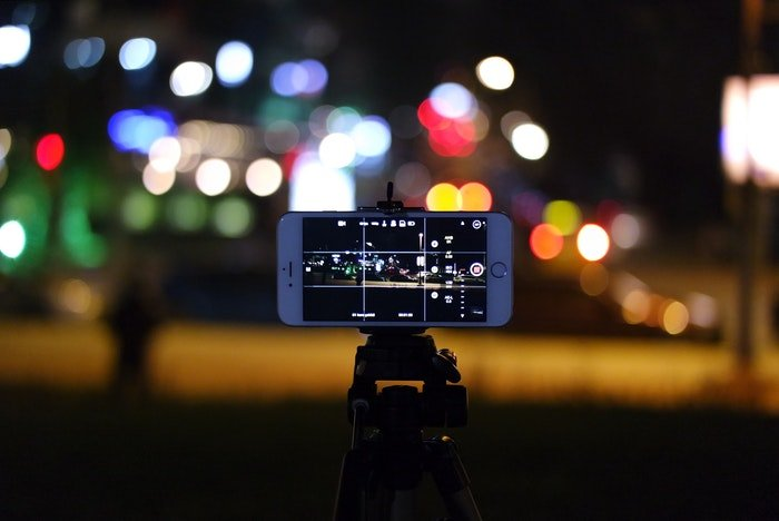 phone mounted on the best iphone tripod against a bokeh background at night