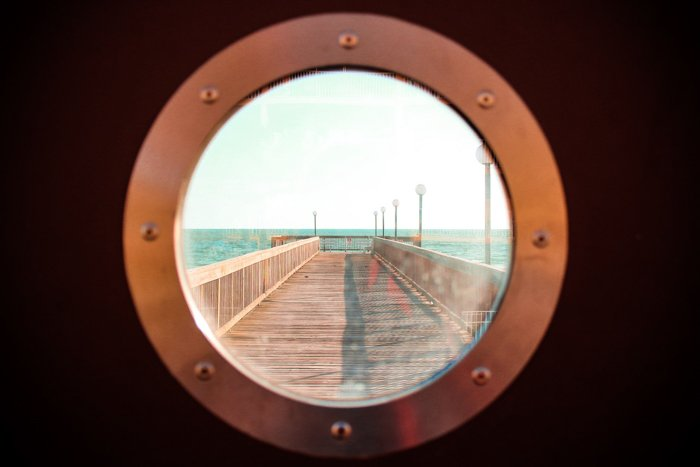 View of a pier through a boat porthole