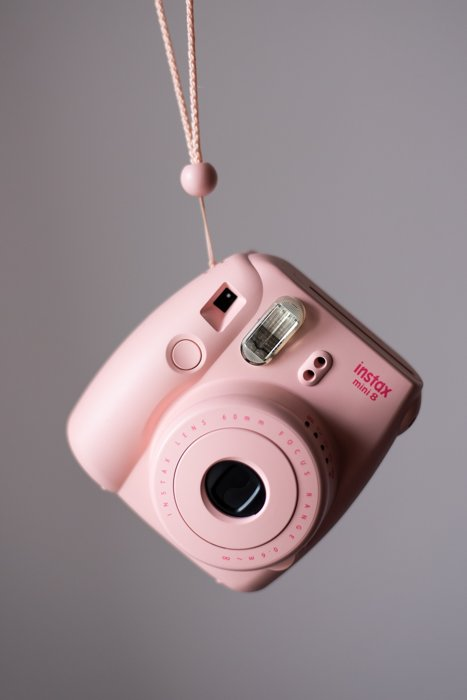 an image of a pink fujifilm instax mini 8 instant film camera dangled from its strap