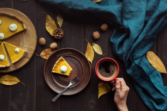 Pumpkin pie and a hot beverage on a table with autumn leaves walnuts and pinecones