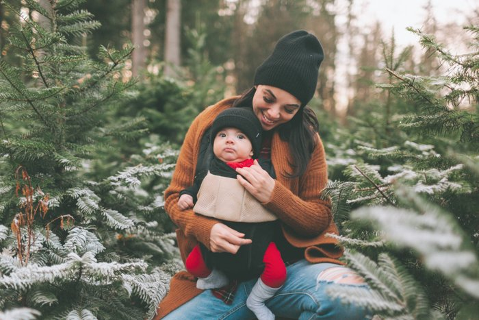 Sweet Christmas photo of a woman holding her baby in front of an outdoor Christmas tree