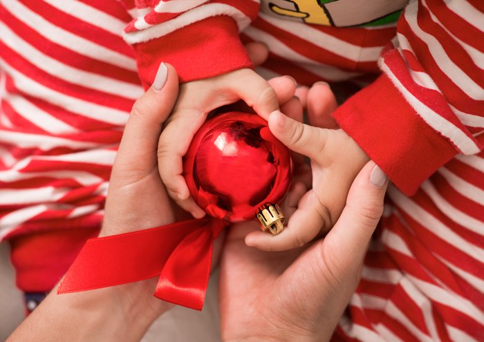Close up of a couple holding their babies hands with a Christmas decoration