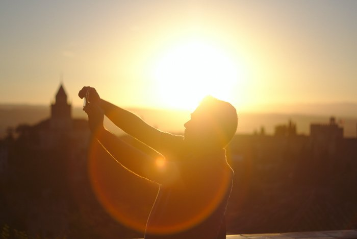 an image of a man on a rooftop with backlighting and lens flare