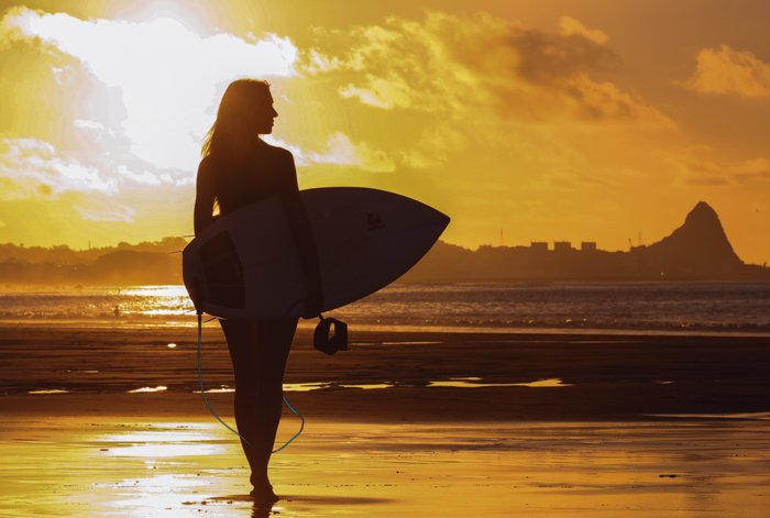 a silhouette of a woman holding a surfboard on the beach with setting sun backlighting