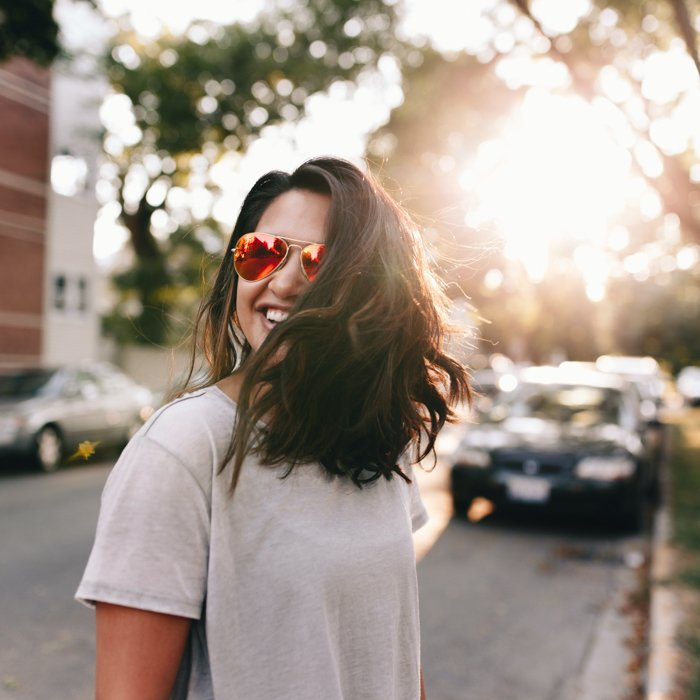 an image of a woman in sunglasses on a city street with setting sun backlighting