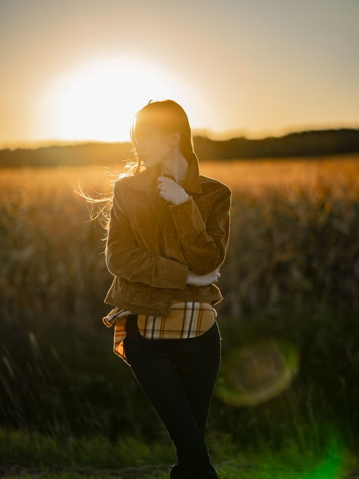 an image of a woman posing in a meadow with setting sun behind her