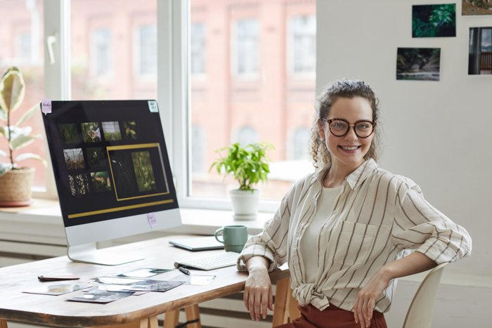 Portrait of young female photographer smiling at camera while posing at desk with photo editing software on computer screen