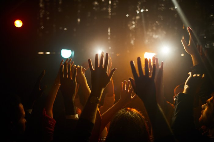 Crowd of people standing in dark club and waving hands in air