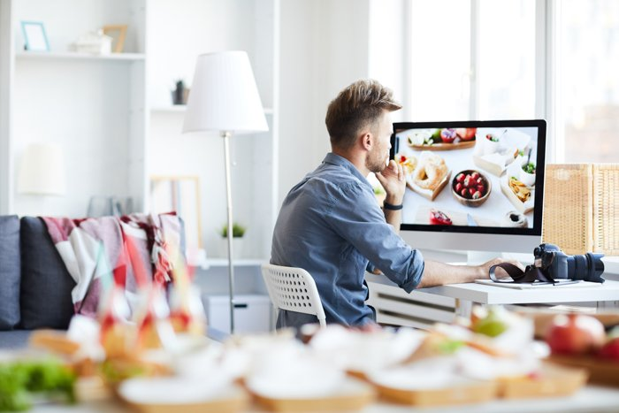 Side view portrait of young photographer editing photos of food sitting at a desk