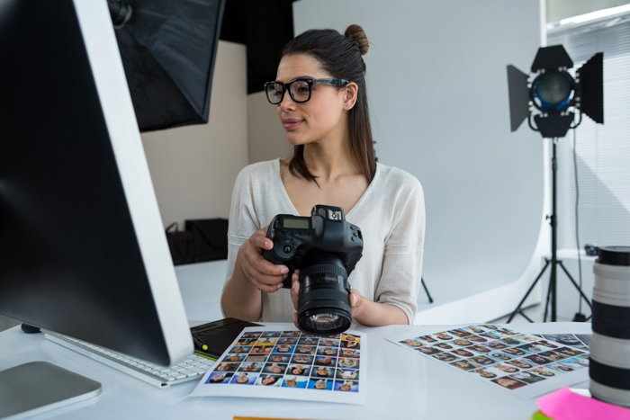 a female photoigrapher holds a camera while looking at her computer screen in the studio