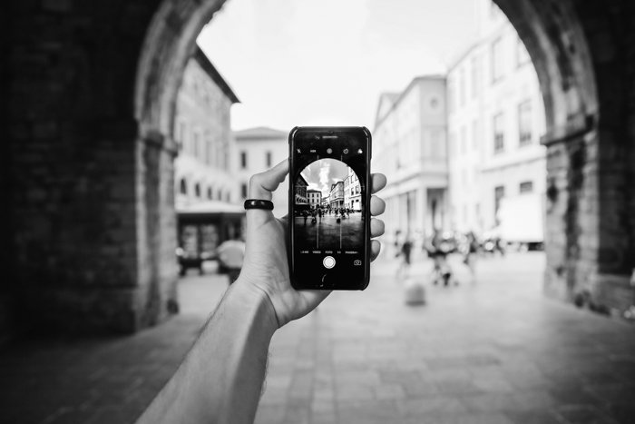 a black and white image of a hand holding a smartphone in an alleyway