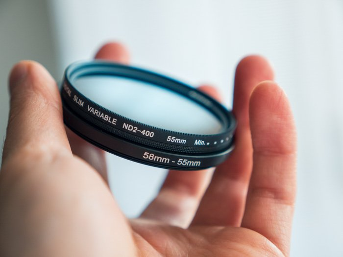 an image of a hand folding a camera lens filter