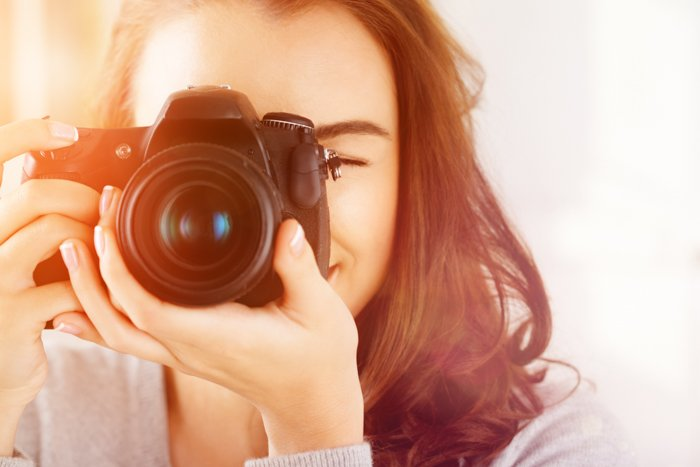a portrait of a young woman holding a camera to her eye