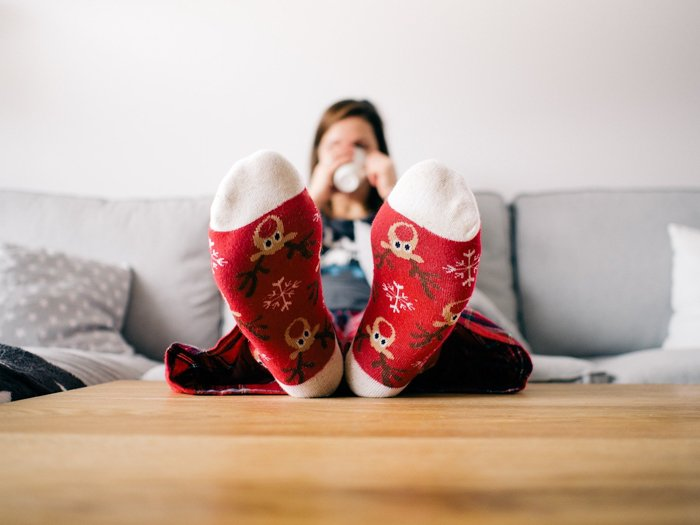 Personal christmas card photo ideas of a woman on a couch in christmas socks