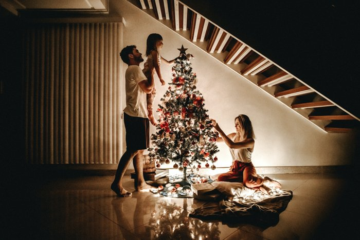 christmas card photo ideas of a family decorating a tree