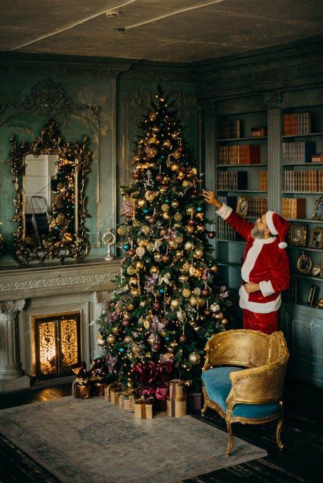 Christmas card photo ideas of Santa decorating a christmas tree