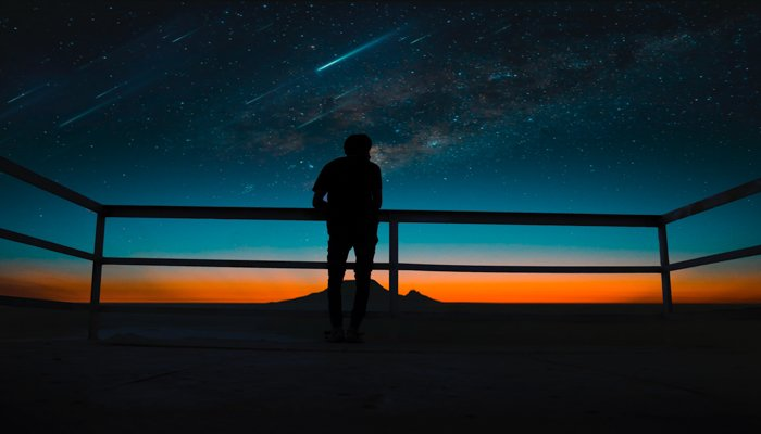 The silhouette of a man watching a meteor shower