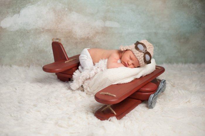 newborn baby posing on an interesting airplane prop
