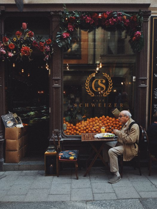 an old man sitting alone and eating outside a restaurant