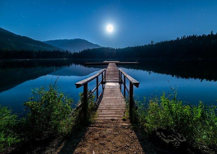 A pier at a lake at night