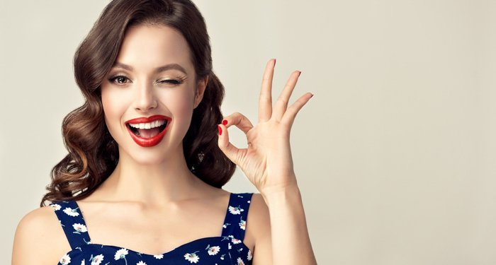 a portrait of a model posed making the ok sign and winking