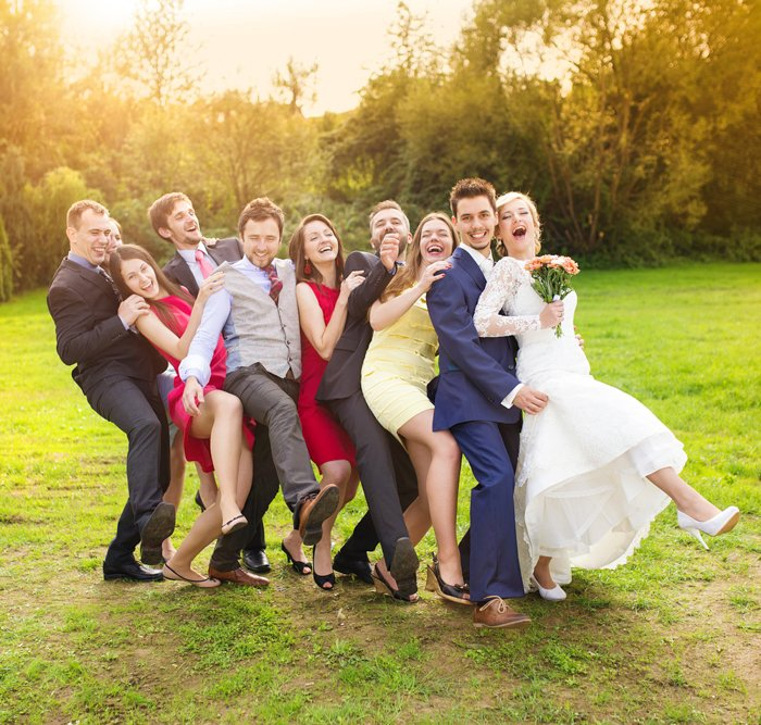several people posing as part of a wedding party