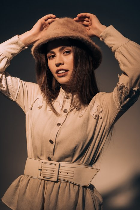 a model posing holding her hands above her head
