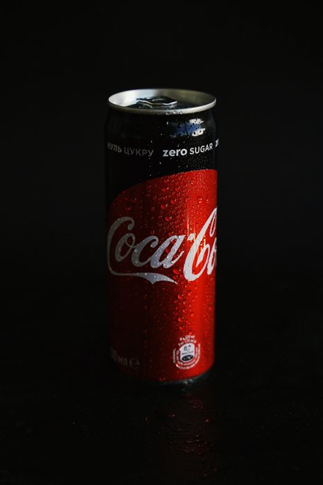 product photography photo of a CocaCola Coke can with a black studio background