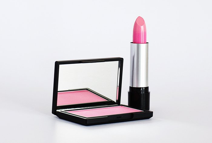 Product photography image of pink lipstick and blush, and case with a mirror