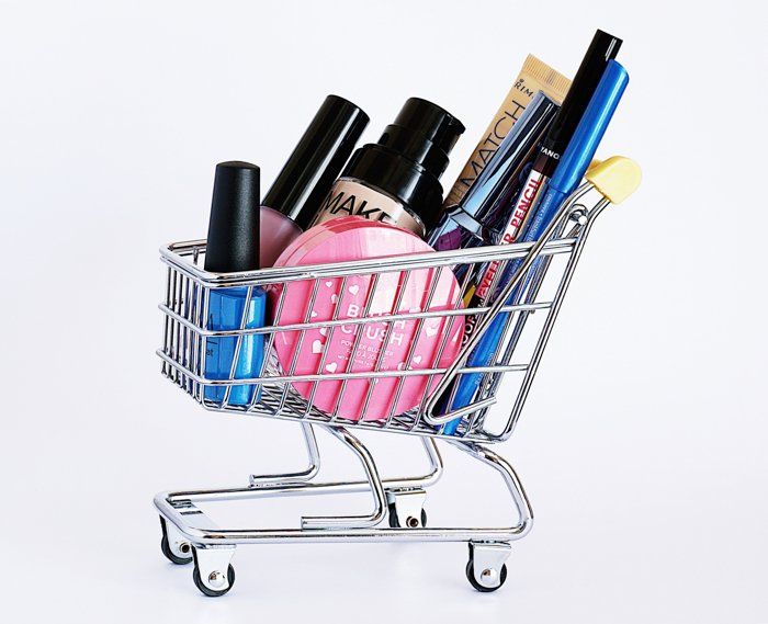 Product photography image of a miniature shopping cart with cosmetic products