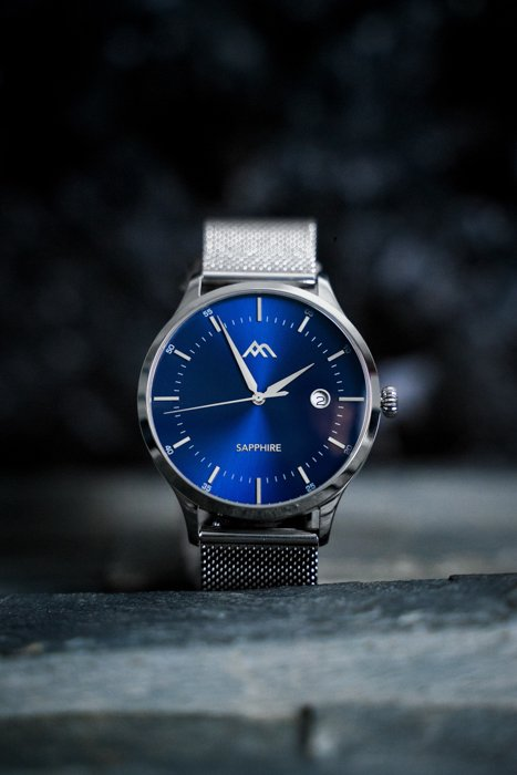 Product photography image of a expensive silver watch with a blue face