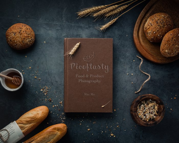 Product photography overhead image of a cookbook on a table with bread and wheat