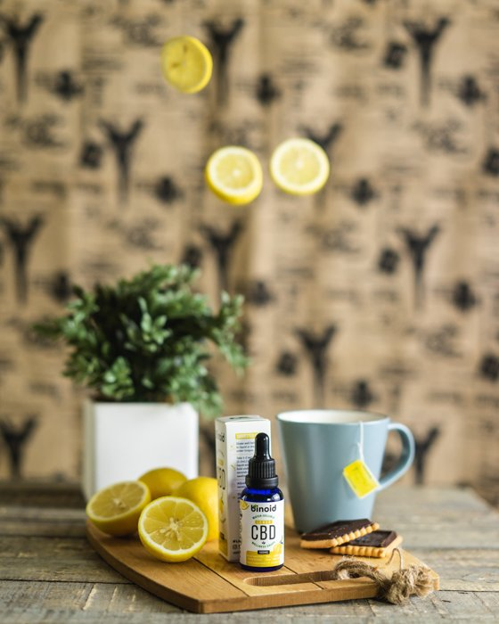 Product photography lifestyle image of a CBD bottle on a dining room table and lemons suspended in the air