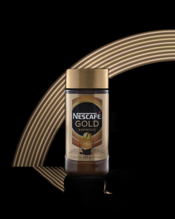 Product photography image of a Nescafe bottle shot in a studio with a gold rainbow in the background