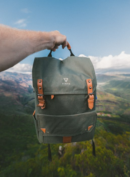 Product photography image of a backpack held up against a blurred natural landscape of sky, hills, and forest