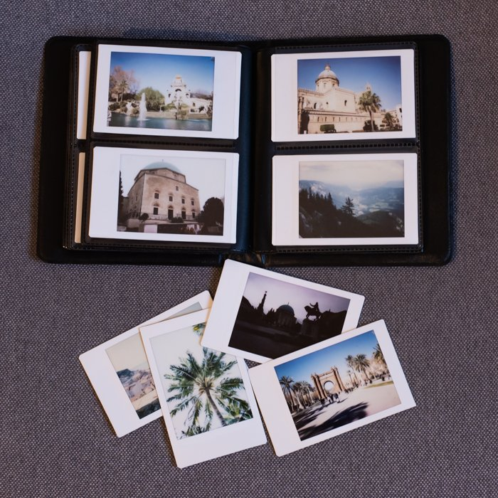 an overhead photo of a fujifilm instax mini 8 photo album with printed instant photos inside and outside