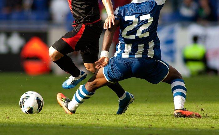 Imagem de dois jogadores de futebol lutando pela bola com uma lente telefoto.