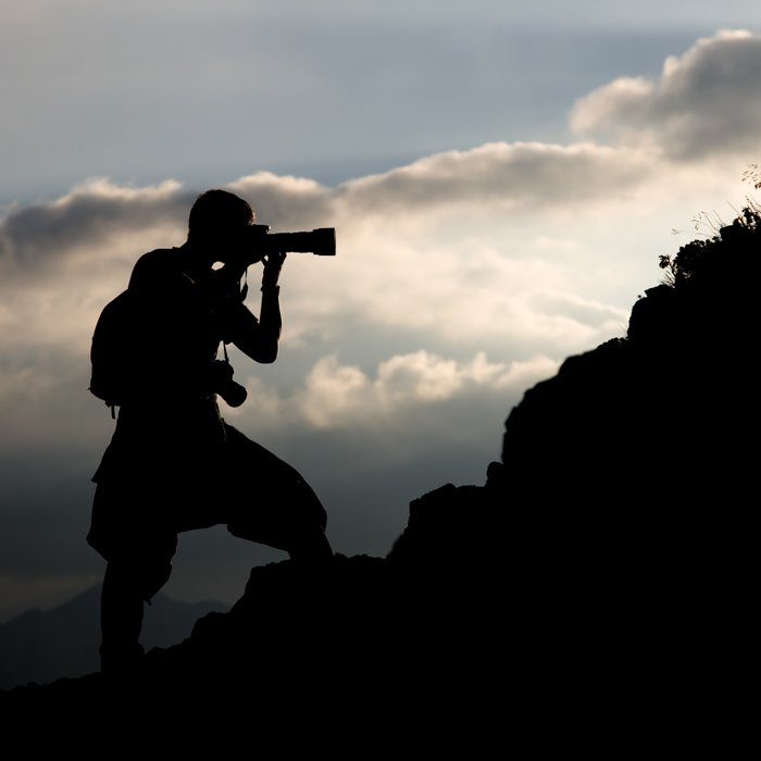 a silhueta de um homem em uma colina fotografando com uma lente teleobjetiva