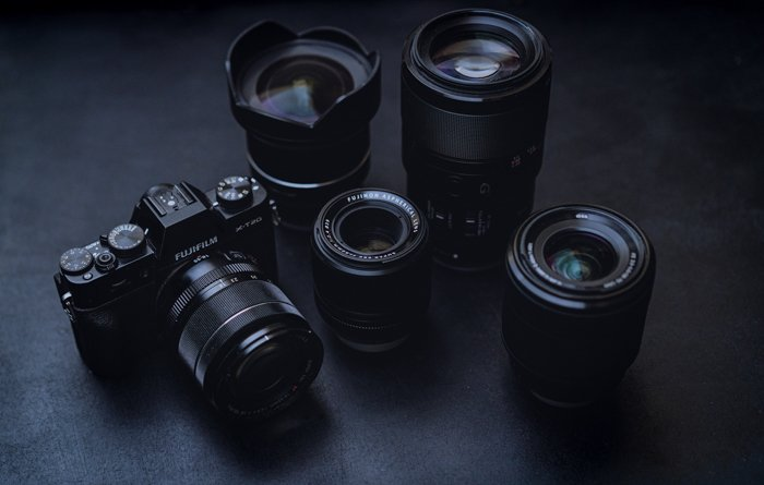 a fujifilm camera with 4 types of lenses resting on a black surface