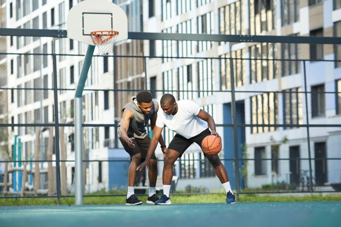 Action shot of two African-American men playing basketball in outdoor court